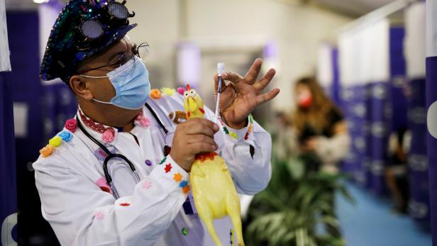 A medical clown holds a toy chicken, syringe and vial as he performs at a temporary Clalit healthcare maintenance organisation (HMO) centre, where vaccinations against the coronavirus disease (COVID-19) are administered, in Herzliya