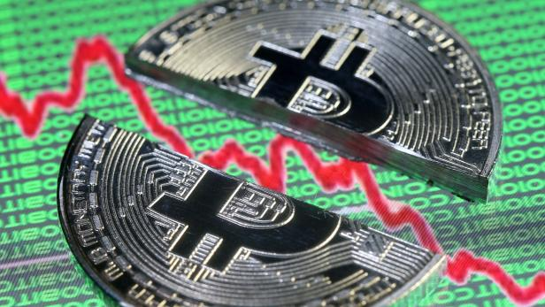 FILE PHOTO: Broken representation of the Bitcoin virtual currency, placed on a monitor that displays stock graph and binary codes, are seen in this illustration picture