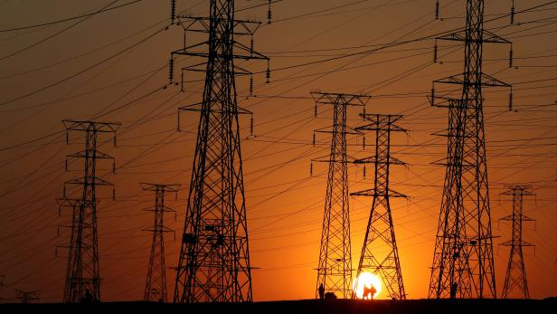 FILE PHOTO: Locals walk past Eskom's electricity pylons as they return from work in Orlando