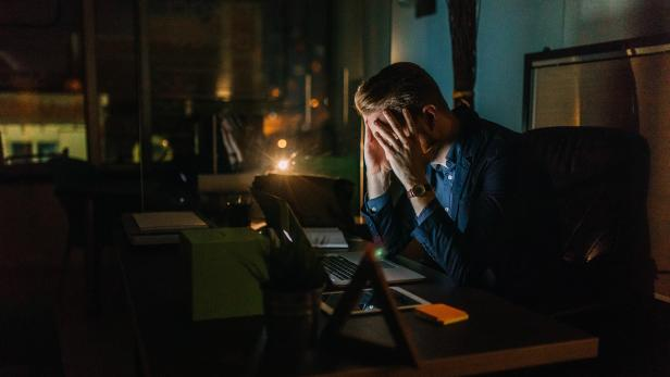 Tired businessman finishing work in office
