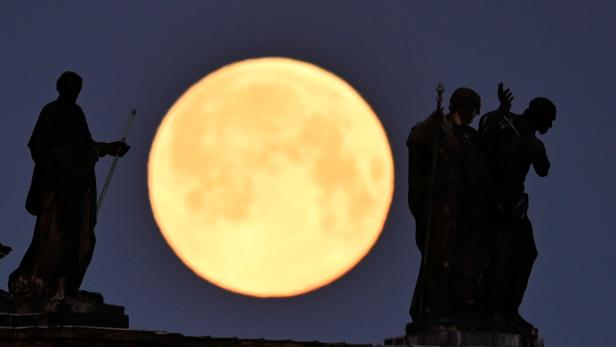 The supermoon is seen behind the sculptures on the roof of the cathedral in Dresden