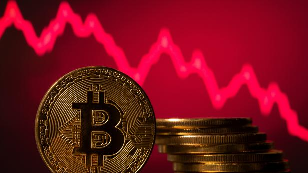 A representations of virtual currency Bitcoin is seen in front of a stock graph in this illustration