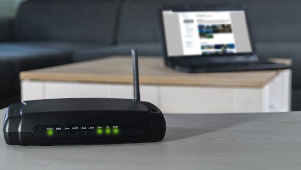 WLAN-Router mit Laptop im Hintergrund