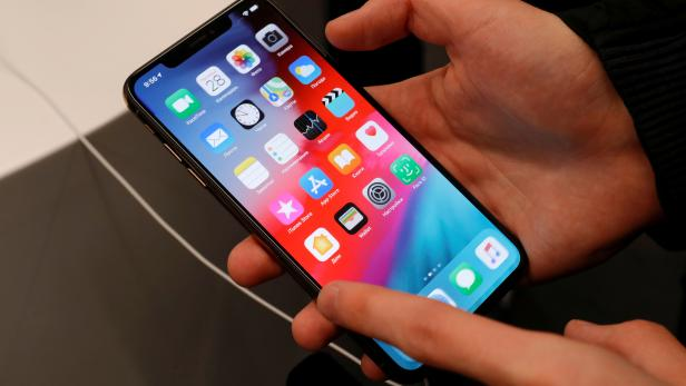 FILE PHOTO: A customer tests a smartphone during the launch of the new iPhone XS and XS Max sales at a shop in Moscow