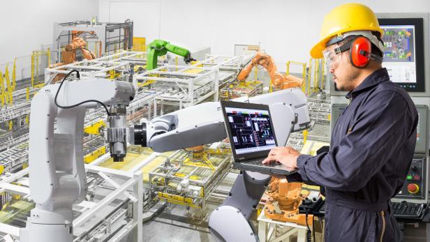 Engineer using computer for maintenance automatic robotic hand machine tool
