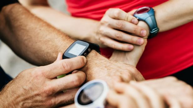 Close Up Of Amateur Athletes Synchronising Smart Watches Together