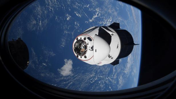 The SpaceX Crew Dragon capsule Endeavor, carrying four astronauts, approaches the International Space Station orbiting the Earth