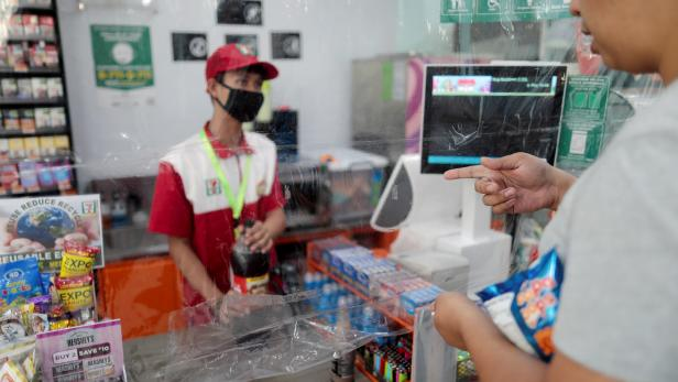 FILE PHOTO: Shops install a makeshift plastic barrier as a protection from coronavirus disease, in Quezon City