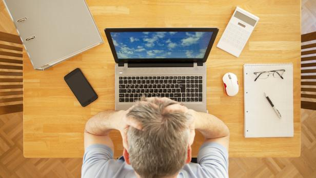 Stressed man sitting at a table with laptop while working from home - view from above