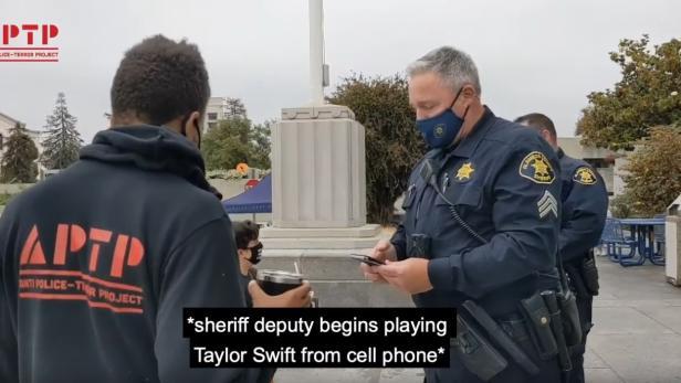 Polizist zückt während eines Gesprächs mit einem Aktivisten sein Smartphone und spielt Musik ab