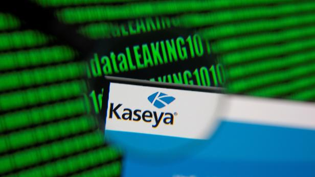 Kaseya's webpage is seen through magnifying glass in front of displayed binary code