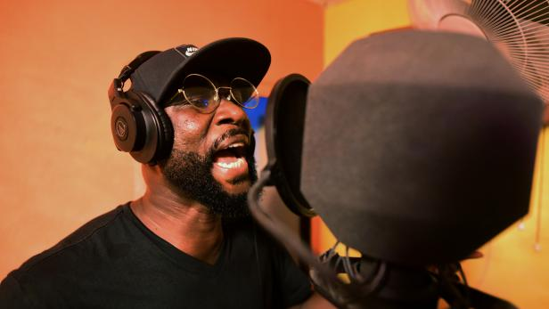 Sierra Leonean musician Emmerson Bockarie sings into a microphone while recording a song at a studio in Freetown,