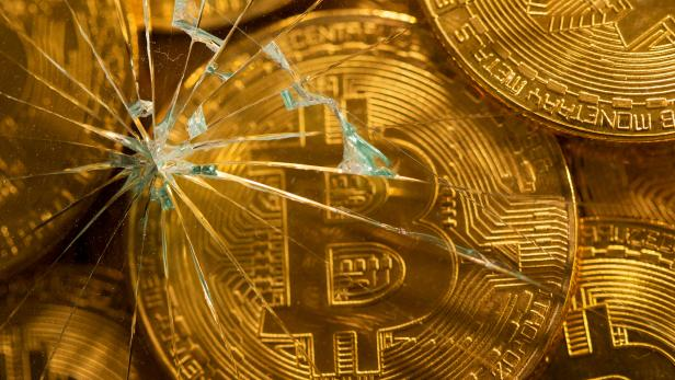 Representations of virtual currency bitcoin are seen through broken glass in this illustration