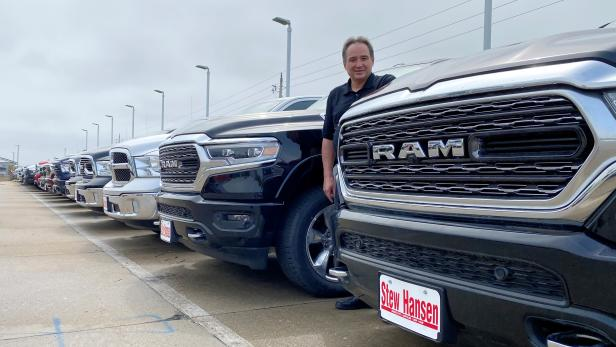 FILE PHOTO: Jerry Bill, general manager of Stew Hansen Chrysler Dodge Jeep Ram, poses among a line of Ram trucks in Urbandale