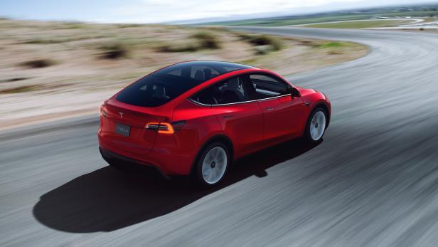 Tesla Model Y von schräg hinten während der Fahrt