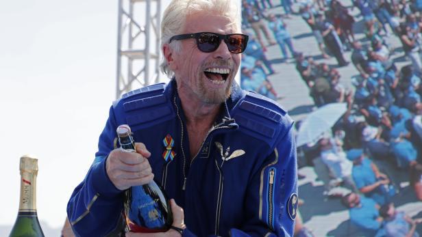 Billionaire entrepreneur Richard Branson prepares to spray champagne at Spaceport America