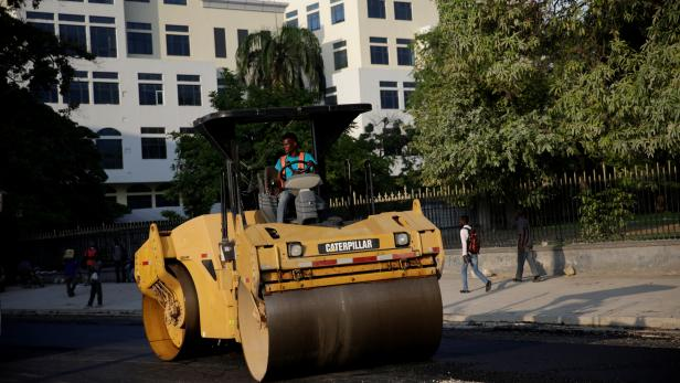 A worker drives a steamroller, with the new building for the Ministry of Economy and Finance in the background, in Port-au-Prince