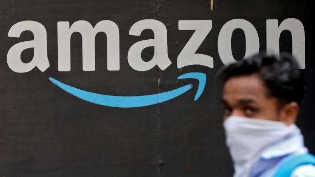 FILE PHOTO: A man walks past an Amazon logo outside the company's collection point in Mumbai