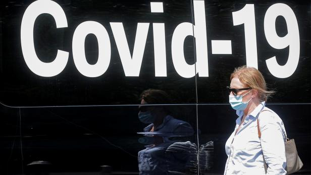 FILE PHOTO: A woman passes by a COVID-19 mobile testing van in New York