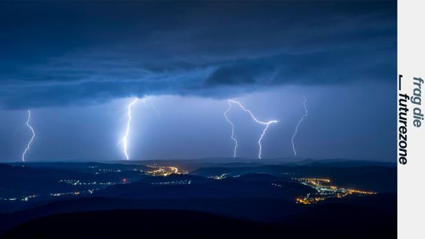 Gewitter in der Nacht über erleuchteten Ortschaften im Gebirge