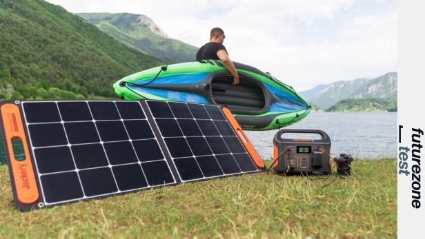 Jackery Explorer 500 und Solarpaneel vor Bergsee mit Kanufahrer