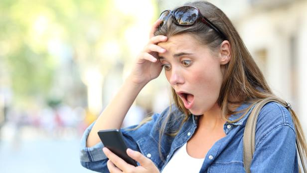 Shocked teen checking phone content in the street
