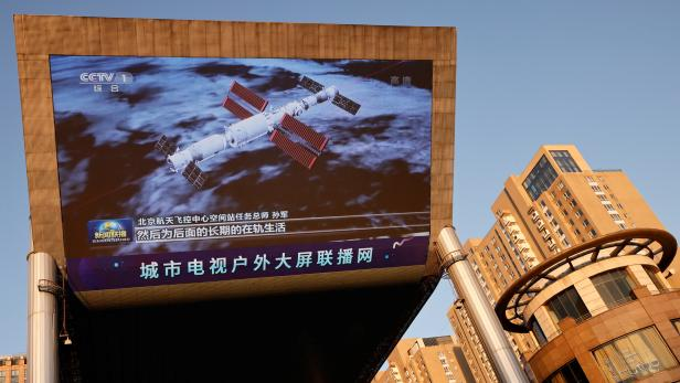 A giant screen shows an image of the Shenzhou-12 manned spacecraft having successfully docked with the Tianhe core module of China's space station, at a shopping mall in Beijing