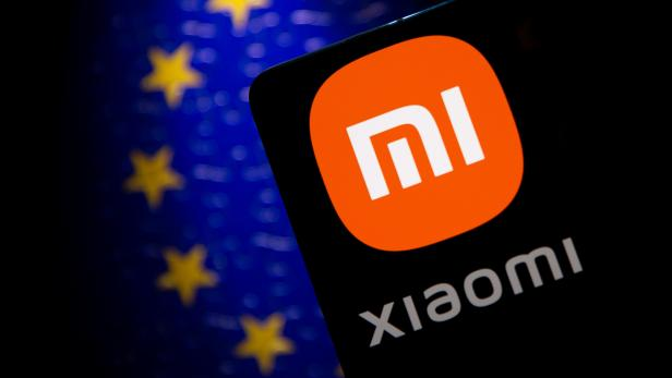 Smartphone with a Xiaomi logo is seen in front of E.U. flag in this illustration