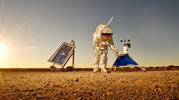 Analog-Astronaut in Raumanzug in Wüste mit Robotern