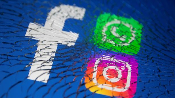 Facebook, Whatsapp and Instagram logos are displayed through broken glass in this illustration