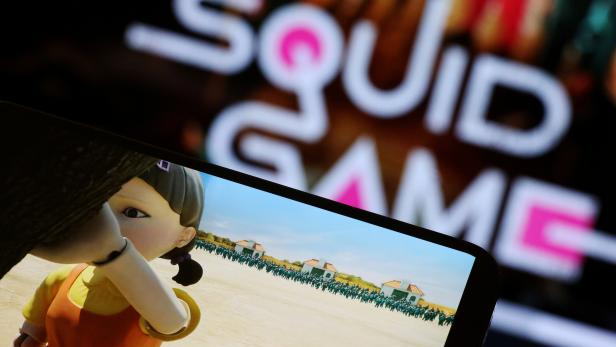 """FILE PHOTO: The Netflix series """"Squid Game"""" is played on a mobile phone in this picture illustration"""