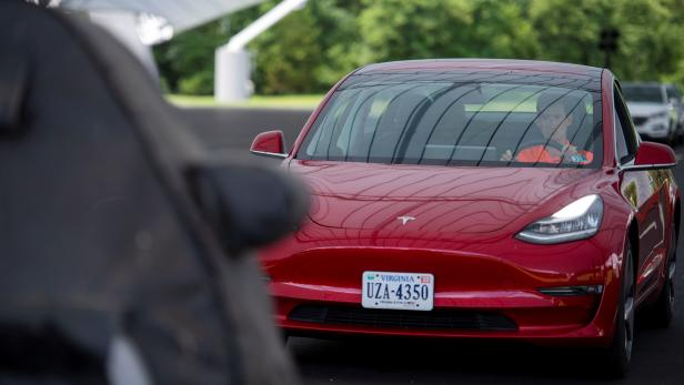 IIHS media relations associate Young demonstrates a front crash prevention test on a Tesla Model 3 at IIHS-HLDI Vehicle Research Center in Ruckersville, Virginia